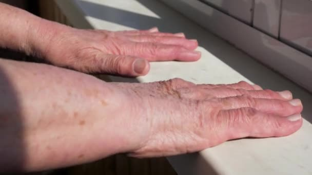 Closeup Of An Old Woman Putting Her Hands With Wrinkles On The Windowsill