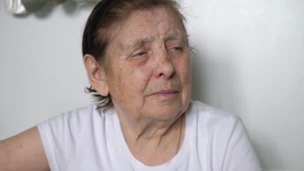 Portrét stařena s vrásky na obličeji, při pohledu na fotoaparát