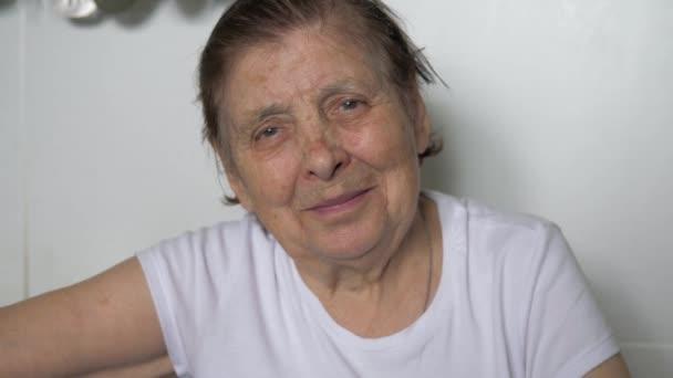 Portrét stařena s vrásky na její tvář při pohledu na fotoaparát a usmívá se
