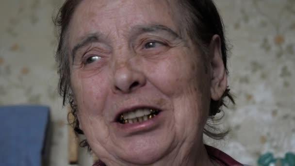 Portrét stařena s vrásky na její tvář při pohledu na fotoaparát a mluví