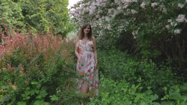 Mladá kráska žena poblíž Kvetoucí keře s krásnými květinami
