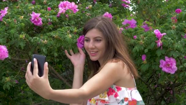 Mladá kráska žena Selfie s květy sedí na lavičce