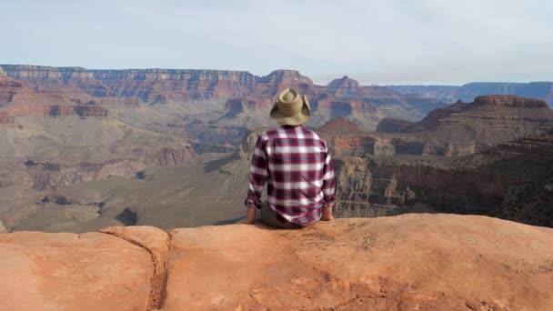 Man Sitting Watching A Amazing View Of Grand Canyon Alone On Edge Of The Abyss