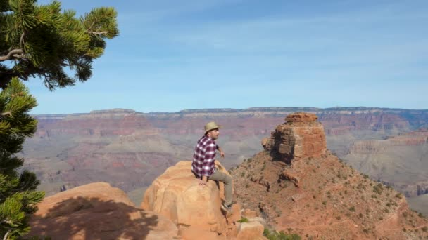 Caucasian Man Sitting On The Rock Edge And Looking Amazing View Of Grand Canyon