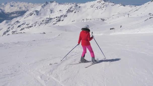 V hnutí začátečník Žena lyžař po dlouhé zatáčky na svahu hory
