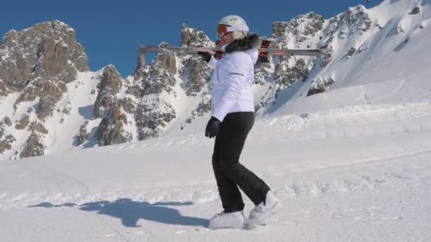 In Mountain Ski Resort A Skier Go Forward With Downhill Ski On Her Shoulder