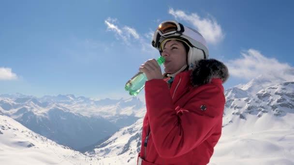 Skifahrerin trinkt sauberes Wasser aus Plastikflasche auf Bergkulisse