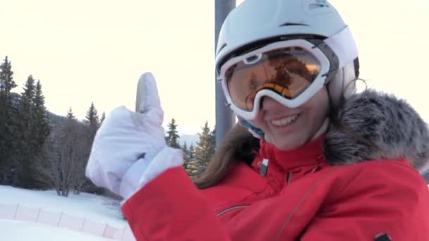 glückliche Skifahrerin besteigt Skilift und zeigt Daumen hoch