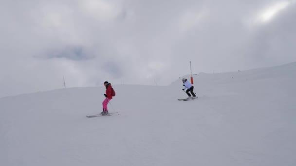 Dvě ženy lyžaře lyžování na obtížnost horské kopce v mlze