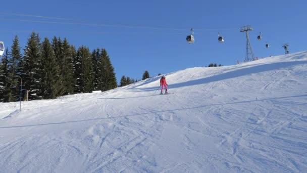 Skifahrer beim Carven auf der Piste in den Bergen im Hintergrund der Standseilbahn
