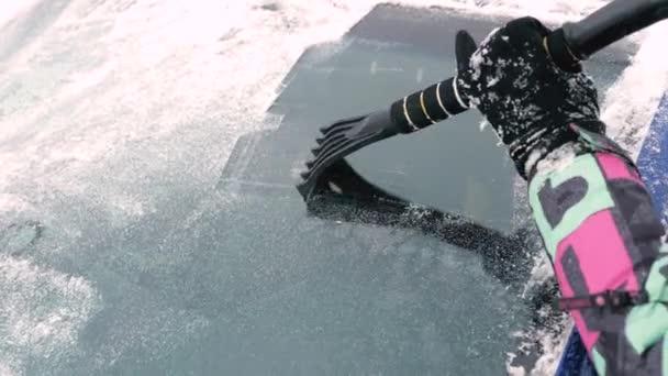Closeup žena rukou čistit přední sklo od sněhu a ledu pomocí škrabky