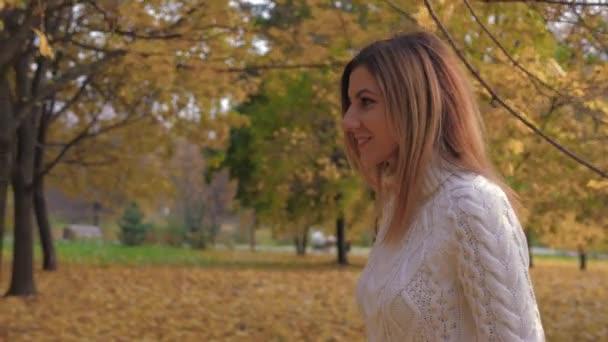 Side View Of A Woman Walking In The Park In The Fall Turns Her Head And Smiles