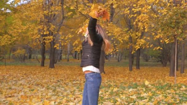 freudige Frau dreht sich im herbstlichen Park um und hält goldgelbe Blätter