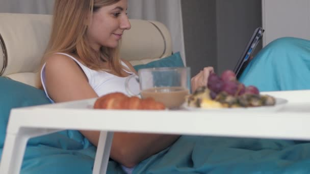 Woman In Bed Uses A Laptop And Near To Her Tray With Breakfast Coffee And Sweets
