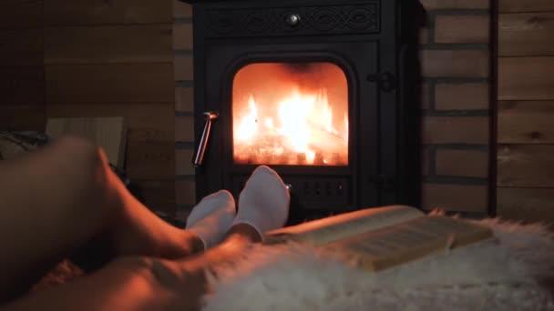 Ženy nohy pohodlně a teple teplo ohně krbu
