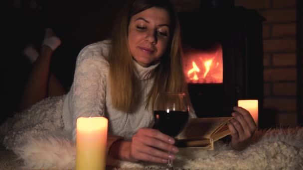 Woman Lies On A Blanket By The Fireplace Drinking Wine And Reading A Book