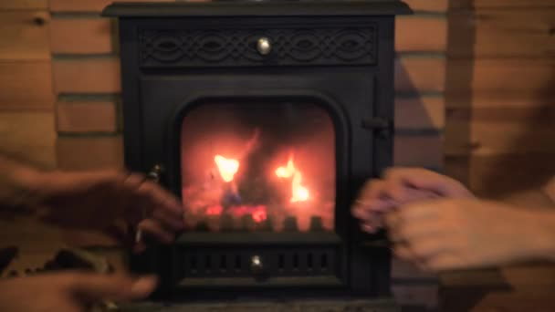 Couple Holding Hands Near The Burning Fireplace