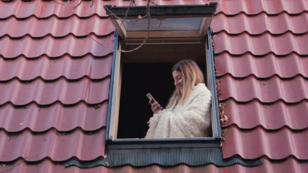 Woman Stands At The Roof Window Of The House And Uses The Phone