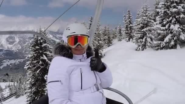 glückliche Skifahrerin steigt mit dem Sessellift auf den Gipfel und zeigt den Daumen nach oben