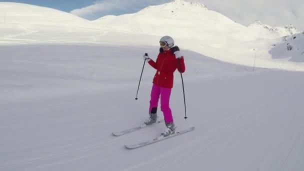 Šťastná žena lyžaře lyžování dolů na svahu v zimě a tančí s rukama