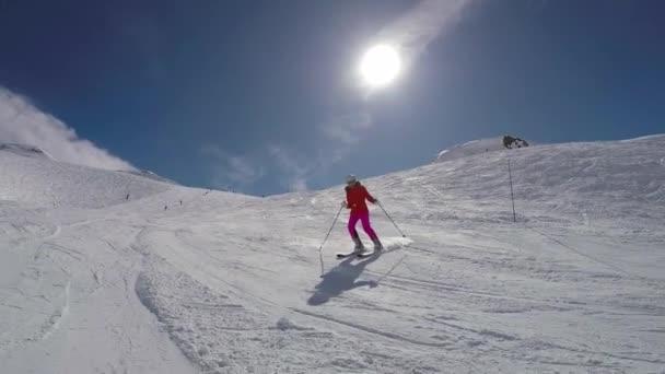 Skirennläuferin auf der Skipiste in den Winterbergen an einem sonnigen Tag