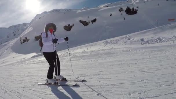 Lyžař v horách na mírném svahu tlačil jeho hole k lyžování dolů