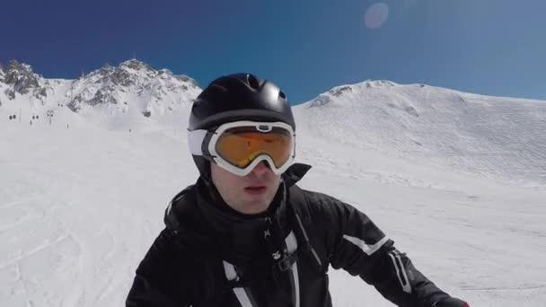 Selfie-Porträt eines Skifahrers in Nahaufnahme, der sich beim Skifahren oft über den Berghang dreht und am Ende der Bremsen eine Menge Adrenalin im Blut hat. Sonneneinstrahlung, Zeitlupe