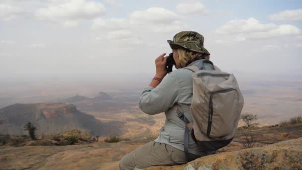 Wanderer am Gipfel des Berges macht Fotos von der malerischen Landschaft