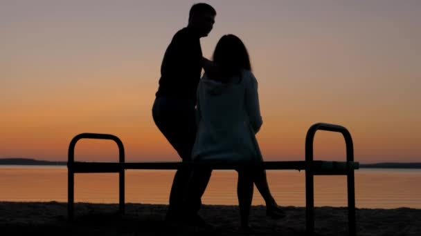 Loving Couple Sitting On A Bench In An Embrace On The Beach And Enjoy The Sunset