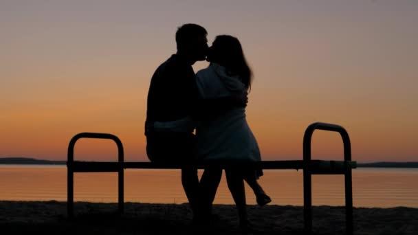 Milující pár sedí na A lavička v objetí na pláži a vychutnejte si Západ slunce