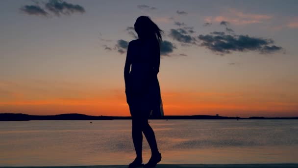 Silhouette Of A Woman Posing At Camera On Background Of Sunset
