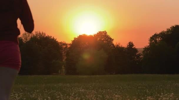 Šťastná žena běží přes pole směrem k západu slunce za letního večera