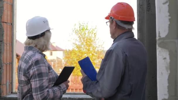 Építő és a vevő egy sisak, a ház építési terv megvitatása