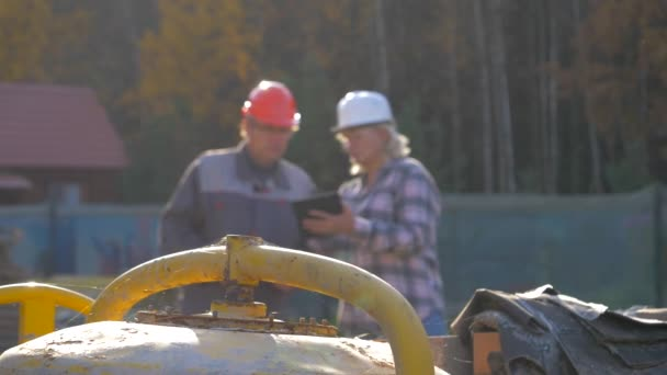 Builder And Client In Helmet Discuss Construction According To Plan Project
