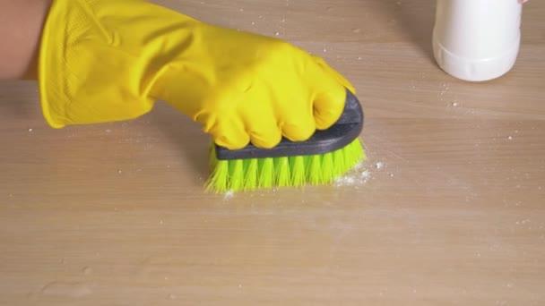 Hospodyňka ruku v gumové rukavici ubrousky špinavý stůl s čistící prášek s kartáčem