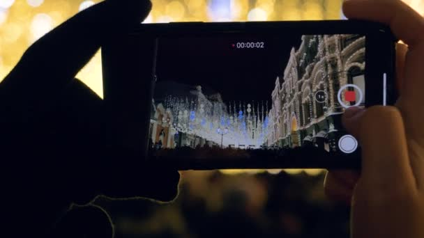 Weihnachtsbeleuchtung auf dem Smartphone und viele Menschen auf dem Platz