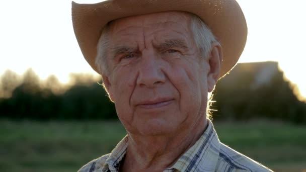 Portrait Of An Elderly Caucasian Farmer Agronomist In A Cowboy Hat On The Field