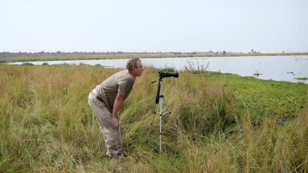 Man Photographer Takes Pictures On Camera Stand On Tripod In Wildlife Of Africa