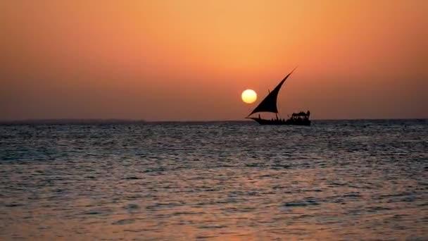 Černá silueta jachtařské lodi plovoucí na moři při západu slunce s velkým červeným sluncem