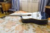Akusztikus gitár szóló ágy alacsony szög lövés a pengető a test alsó