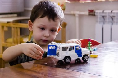a little boy is playing with a toy police car