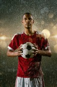 Soccer player on professional soccer night rain stadium. Dirty player in rain drops with football ball