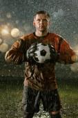 Soccer goalkeeper on professional soccer night rain stadium. Dirty player in rain drops with football ball
