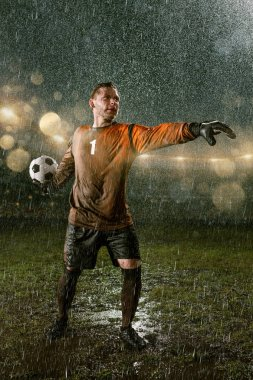 Soccer goalkeeper on professional soccer night rain stadium. Dirty player in rain drops with football ball