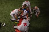 Během hry se poranila noha fotbalisty. Sportovní lékaři poskytují první pomoc hráči na profesionálním fotbalovém hřišti