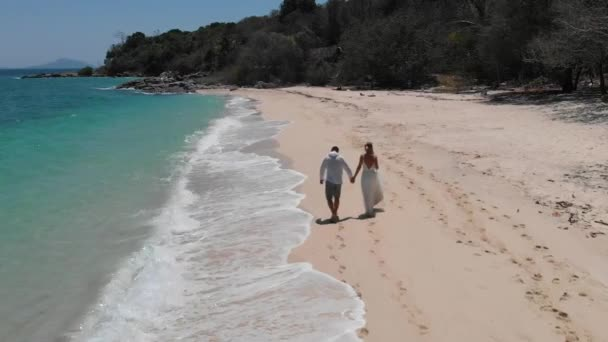 chlapec a dívka běží po pláži tropického oceánu