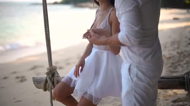 kluk a dívka se houpat na pláži