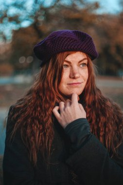 Portrait of red haired woman in hat in the autumn park. Photo made in dark key.