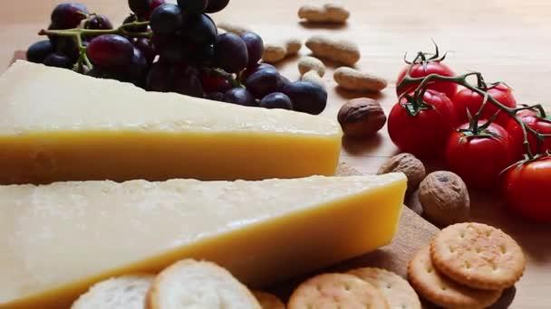 Sýr a třešňová rajčata, sušenku. Čerstvá třešňová rajčata a ořechy na dřevěném pozadí.