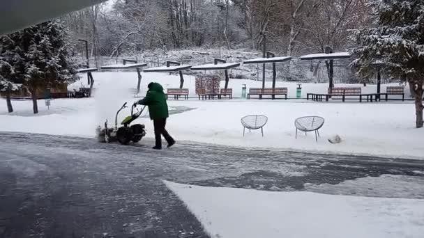 Odstranění sněhu. Sníh se snímá sněhovou frézu. Muž Odstraňuji sníh.